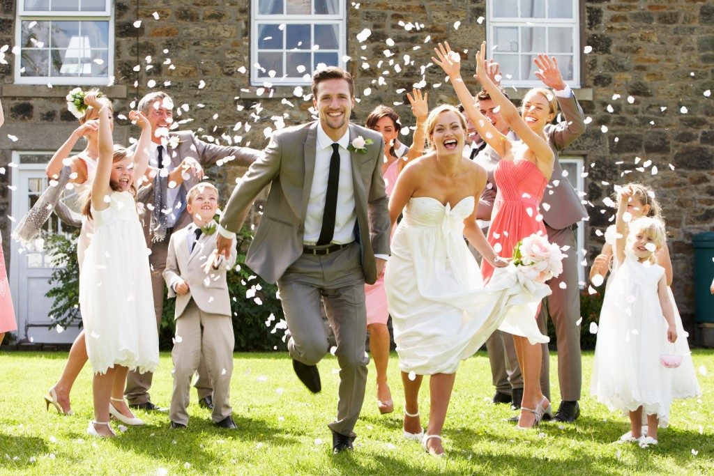 Guest throwing confetti over bride and groom