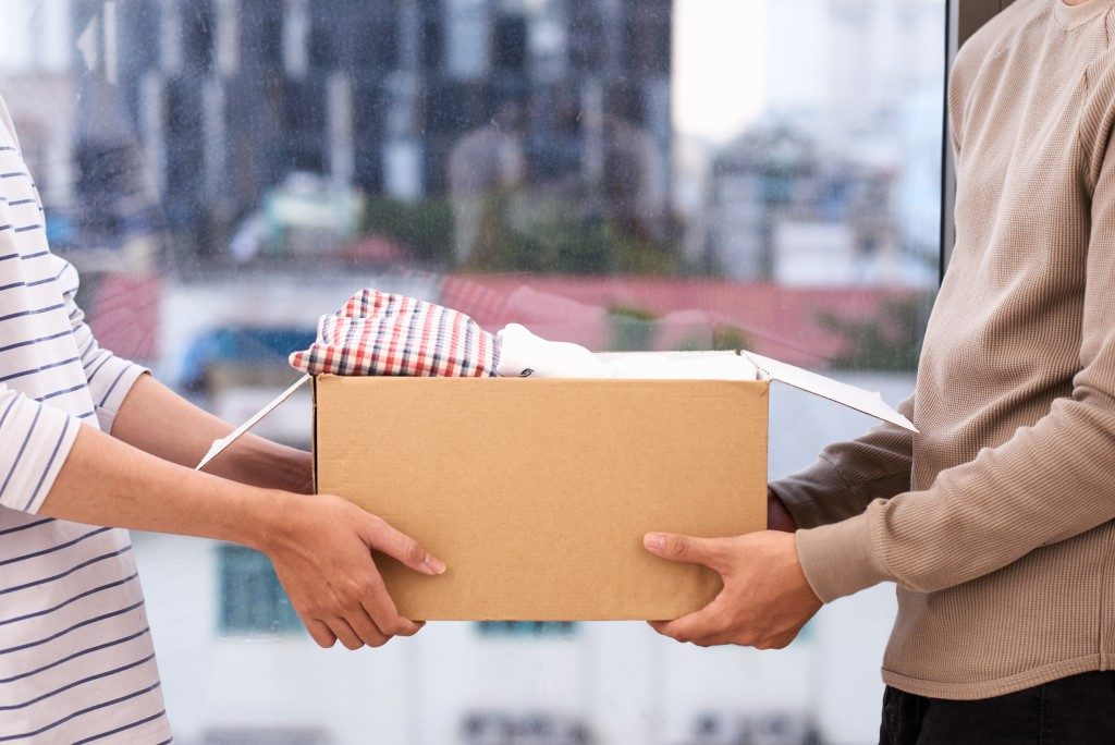 woman handing box to other person