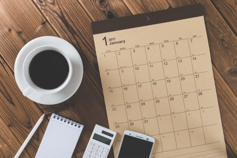 calendar, coffee, phone, calculator and notepad on a wood table