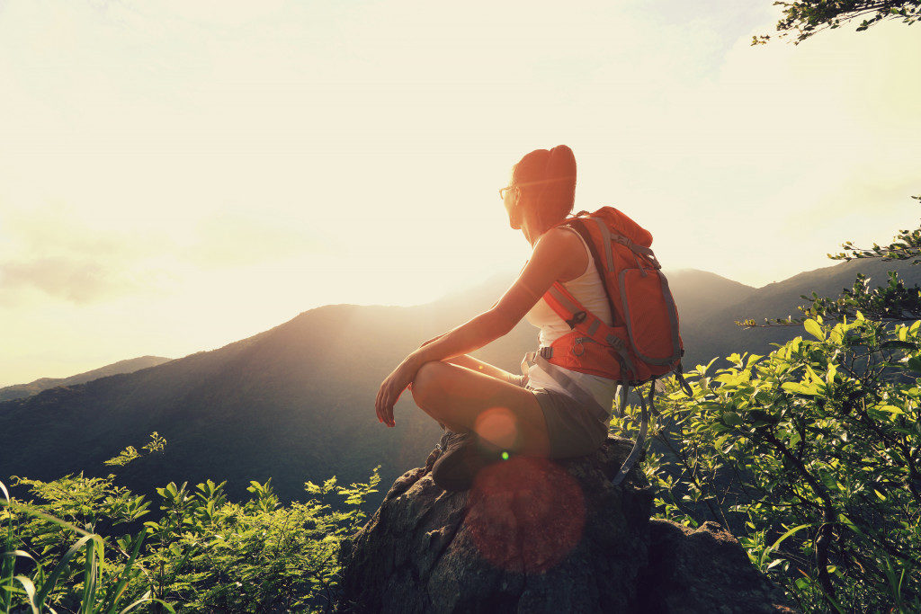 woman backpacker sit on sunrise mountain